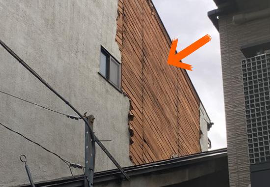 大きく剥離しているモルタル外壁の写真