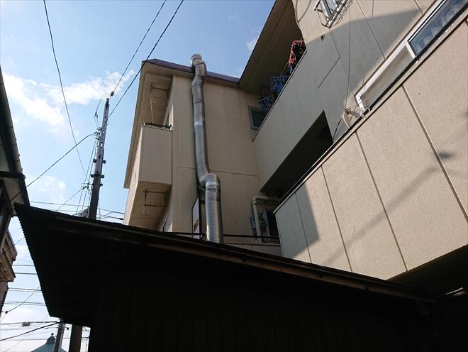 築30年以上経った3階建てのアパートです。1階には飲食のテナントがあり、ダクトが3階屋上まで伸びているのが分かります。